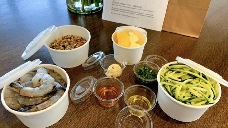 Des contenants avec crevettes, courgettes, riz, sauce et condiments disposés sur une table.