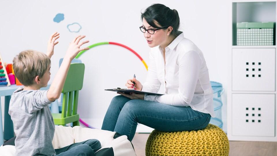 Un jeune garçon discute avec une psychologue.