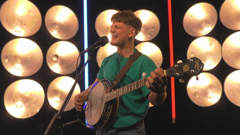 Le jeune homme chante dans un micro sur pied et s'accompagne au banjo sur un plateau de télévision.