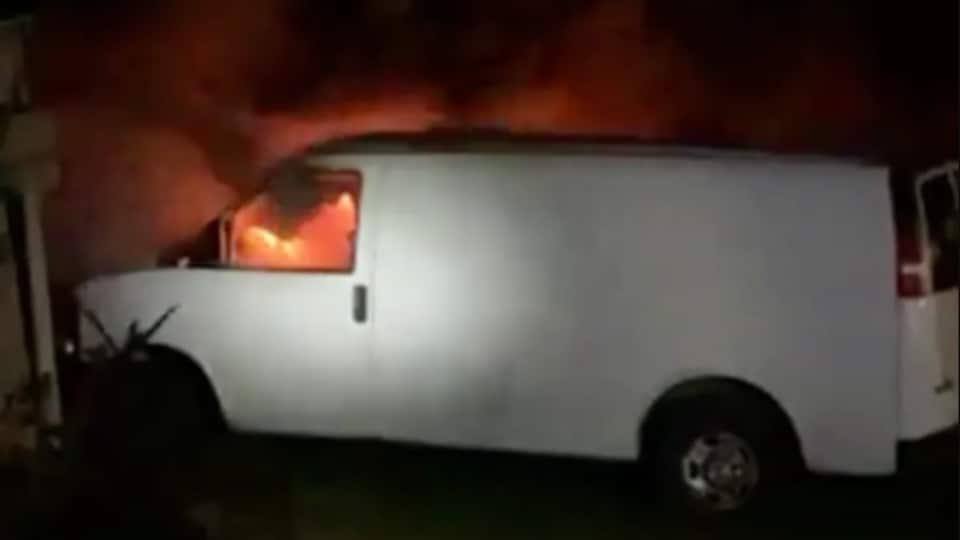Le véhicule en flammes en pleine nuit.