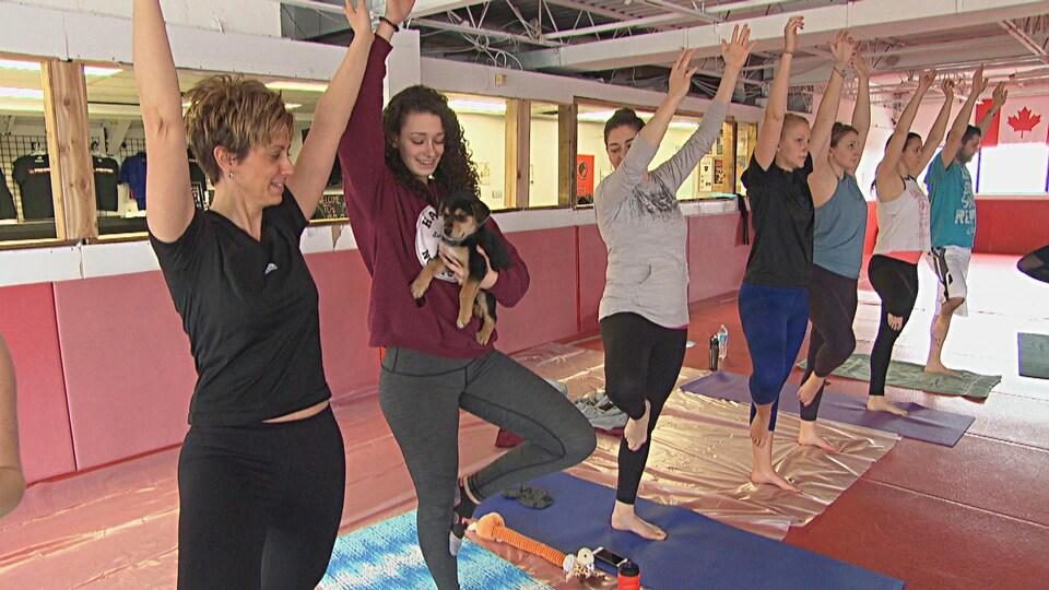 Une femme tient un chiot en prenant une pose de yoga.
