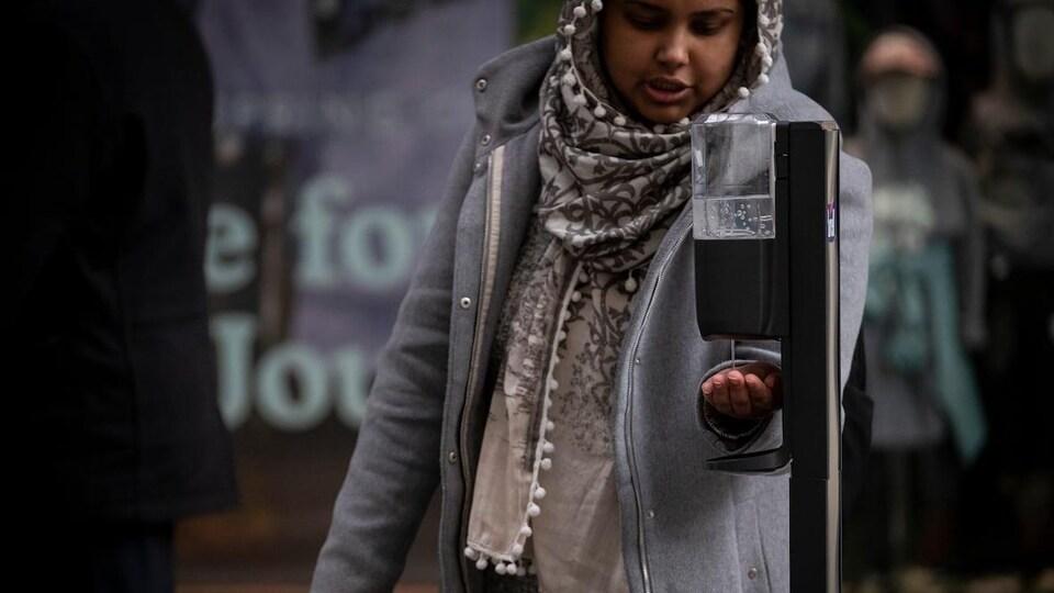 Une femme devant un distributeur du produit