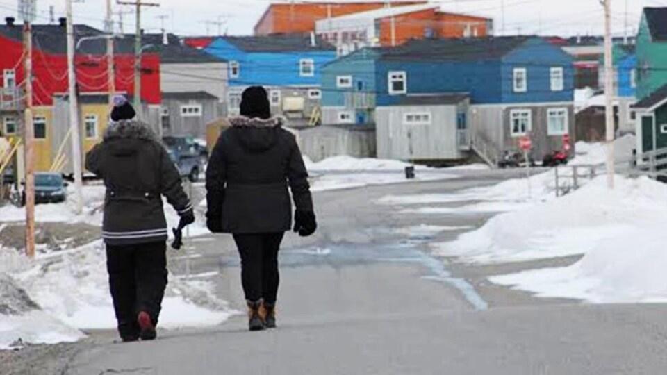 On voit une rue de Puvirnituq. Deux personnes, vues de dos, marchent.