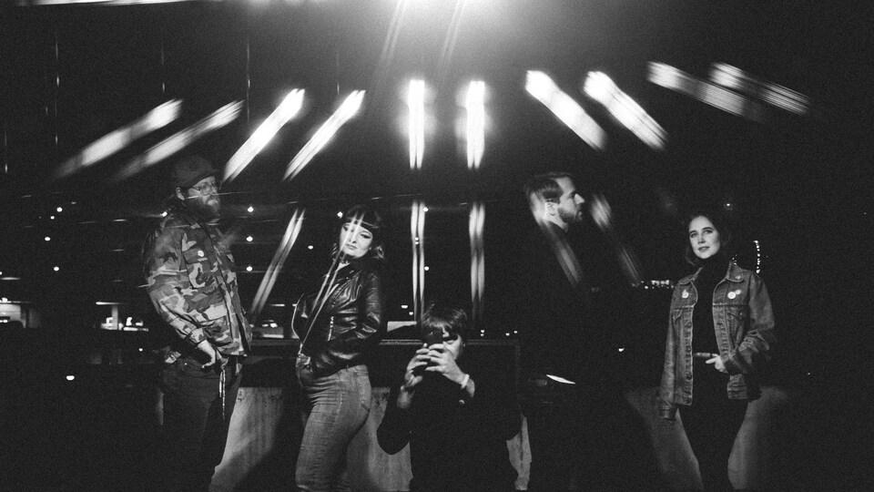 Une image noir et blanc, en extérieur, montre des membres du groupe sous des projecteurs.