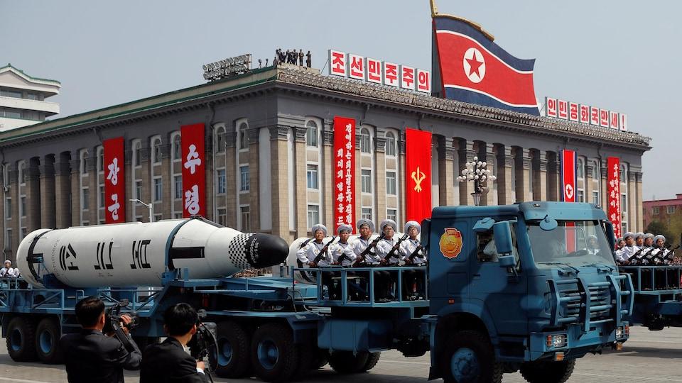 Un camion militaire dans lequel sont assis quelques sodats de la marine nord-coréeen défile dans les rues de Pyongyang avec, derrière eux, un énorme missile.