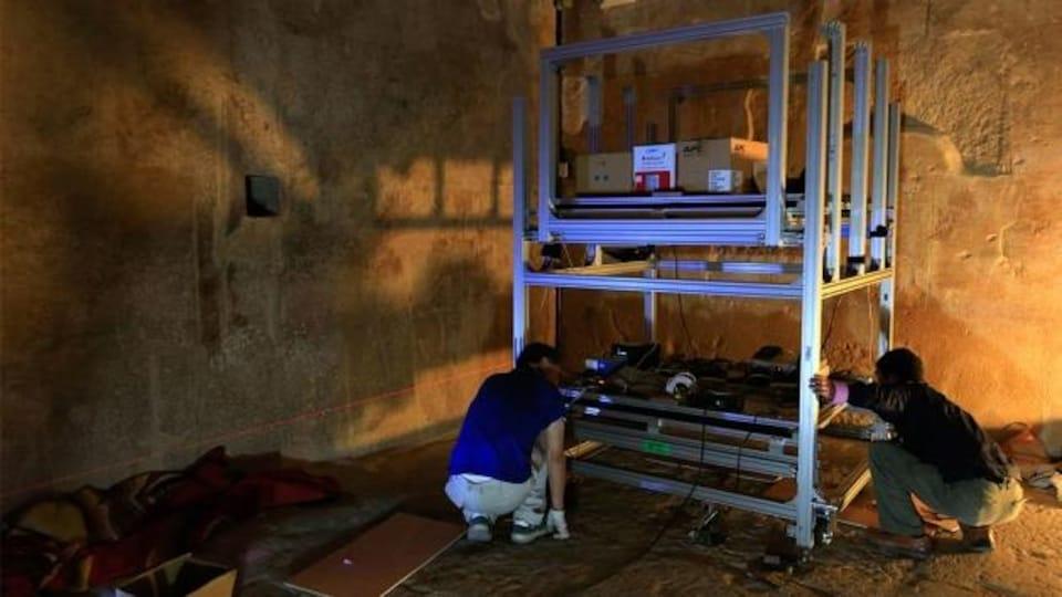 Deux chercheurs ajustent l'appareil servant à détecter les muons circulant à travers la pyramide.