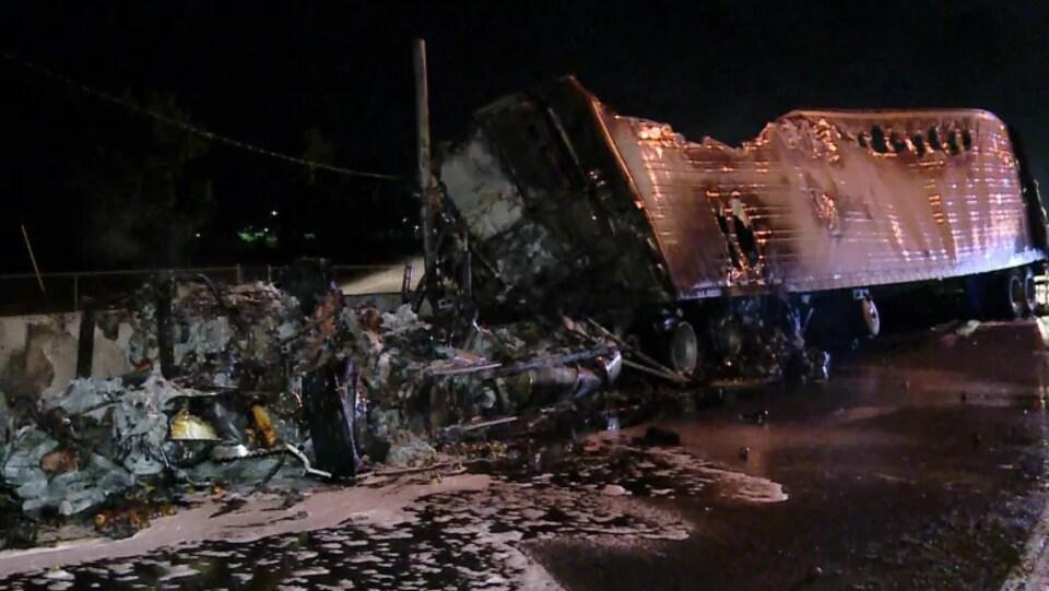 Photo de débris et de la remorque d'un camion brûlés.