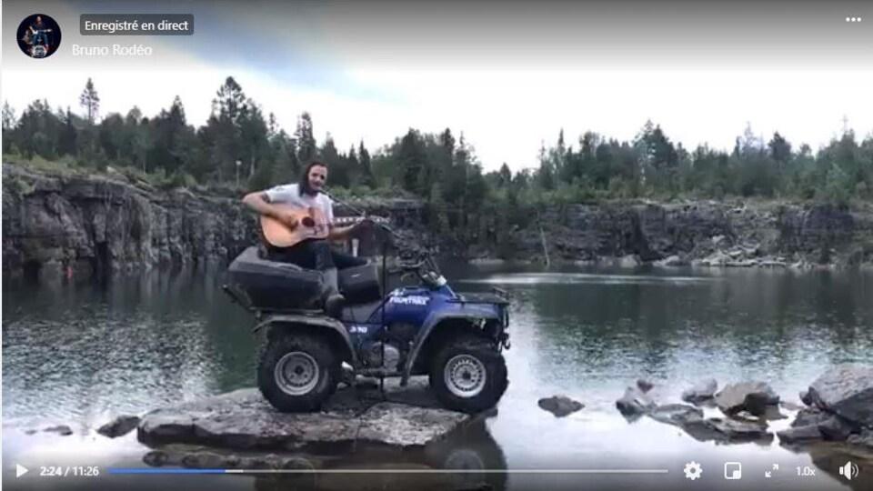 Un chanteur monté sur un quad devant un lac.
