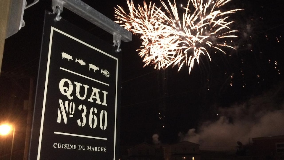 L'affiche d'un restaurant avec un feu d'artifice dans le ciel du soir.