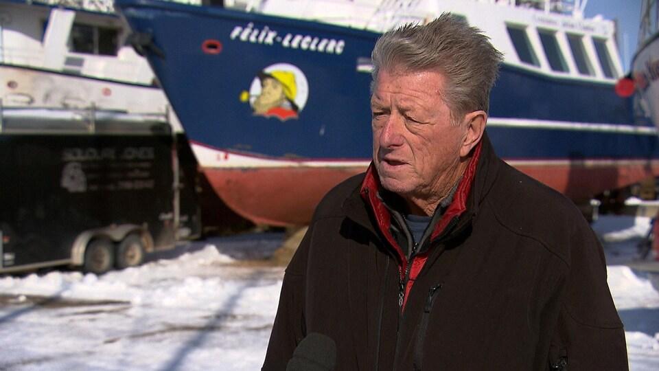 Un homme dehors l'hiver avec un bateau en arrière-plan.