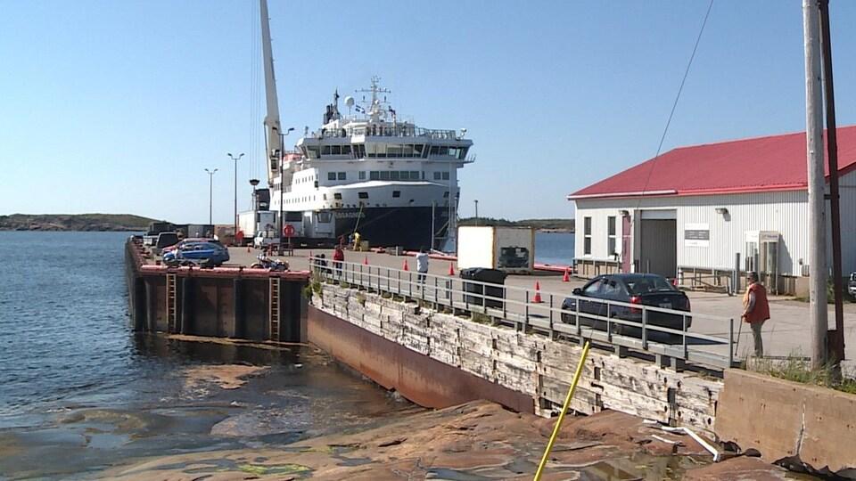 Le navire Bella-Desgagnés est accosté au quai, près d'un bâtiment.