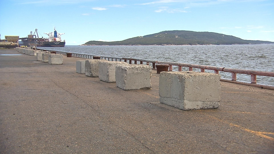 Des blocs de béton sont alignés le long du quai.