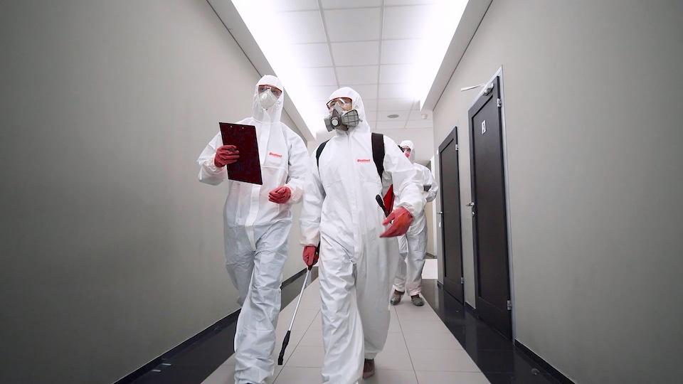 Des employés de qualinet sont vêtus d'un habit de protection blanc.
