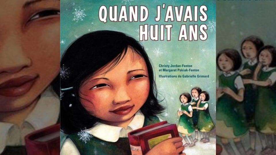 Une fillette tient un livre et trois autres la regardent.