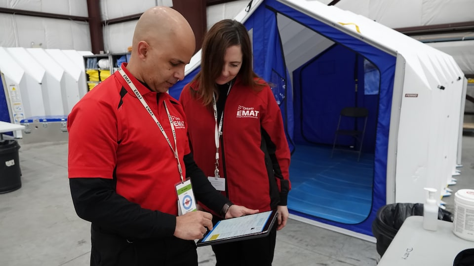 Deux personnes qui notent des informations sur une tablette dans un entrepôt.