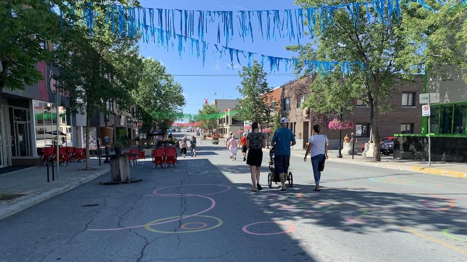 Des piétons marchent sur la rue Principale de Rouyn-Noranda, décorée.