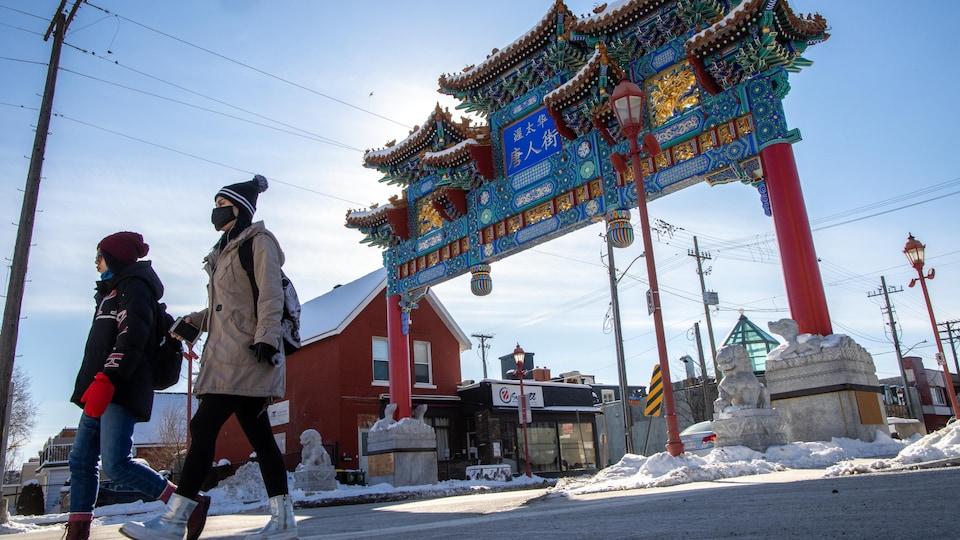 Deux femmes portant le masque dans le quartier chinois d'Ottawa. Derrière elle, on voit l'Arche qui indique l'entrée du quartier chinois.