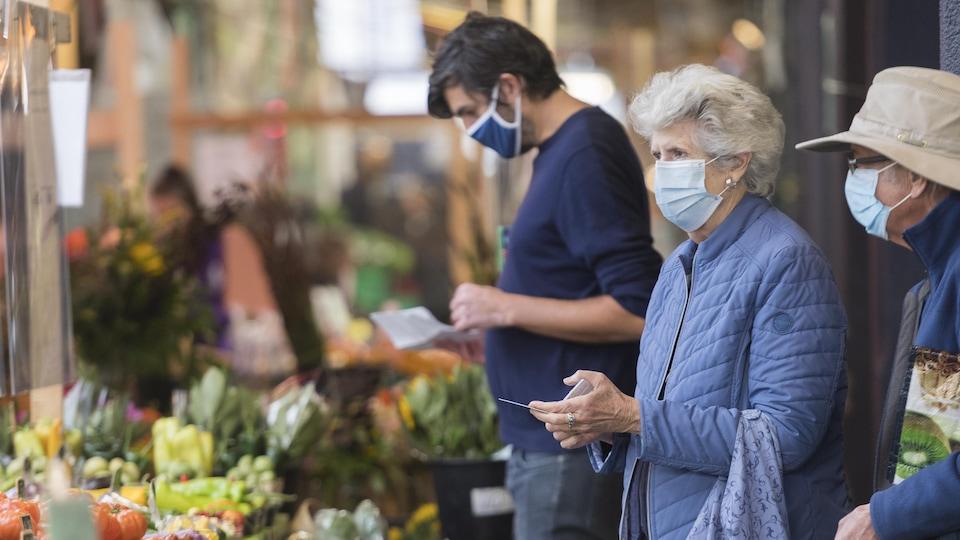 Des personnes devant les étalages d'un marché.