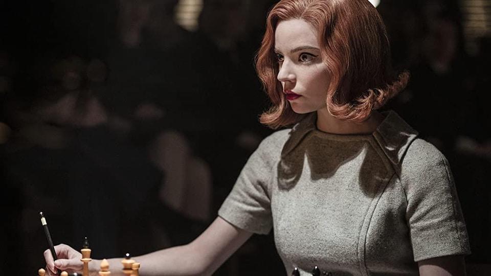 La femme est attablée devant un jeu d'échecs.