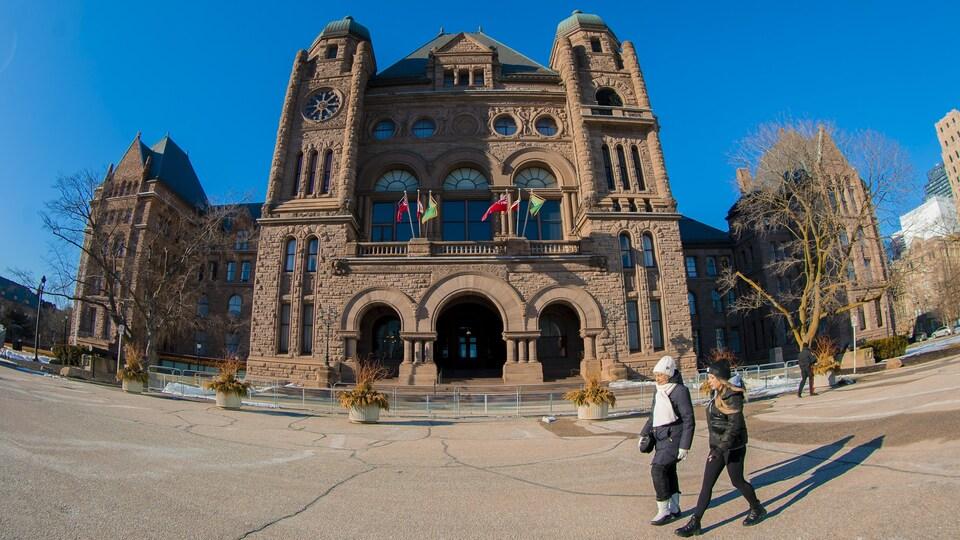 Deux femmes marchent devant l'édifice de l'Assemblée législative de l'Ontario.