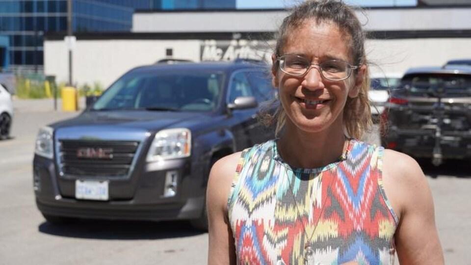 Une femme est debout dans le stationnement du salon de quilles McArthur dans Vanier. Derrière elle, des voitures sont stationnées.