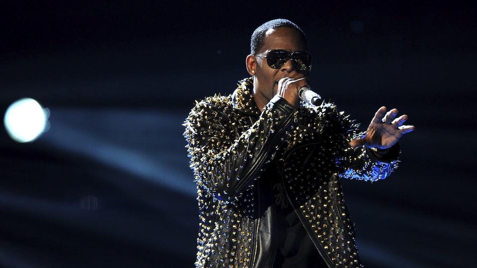Le chanteur R. Kelly donne un spectacle sur un scène, un micro à la main.