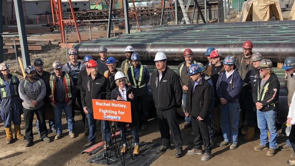 Rachel Notley, avec un casque et des bottes de travail est debout dans un chantier, entourée d'ouvriers. Des tronçons de pipeline sont visibles en arrière-plan.