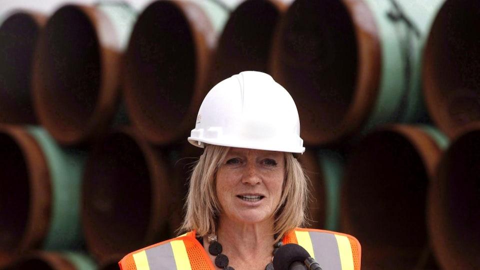Rachel Notley qui porte un casque de construction devant des tuyaux de pipeline.