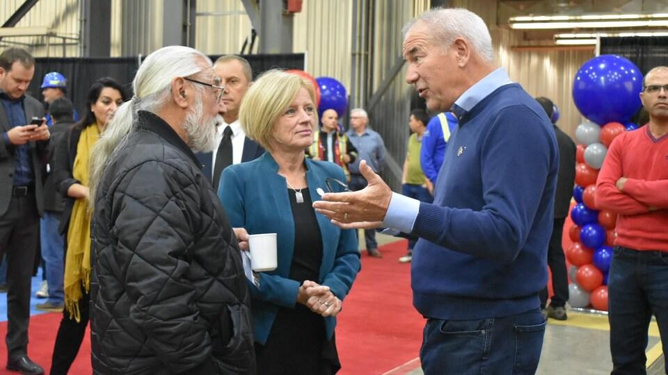 La première ministre de l'Alberta, Rachel Notley, et le PDG de Suncor Energy, Steve Williams (à droite), discutent avec un dignitaire qui a participé à la cérémonie d'ouverture de la mine Fort Hills, le 10 septembre 2018.