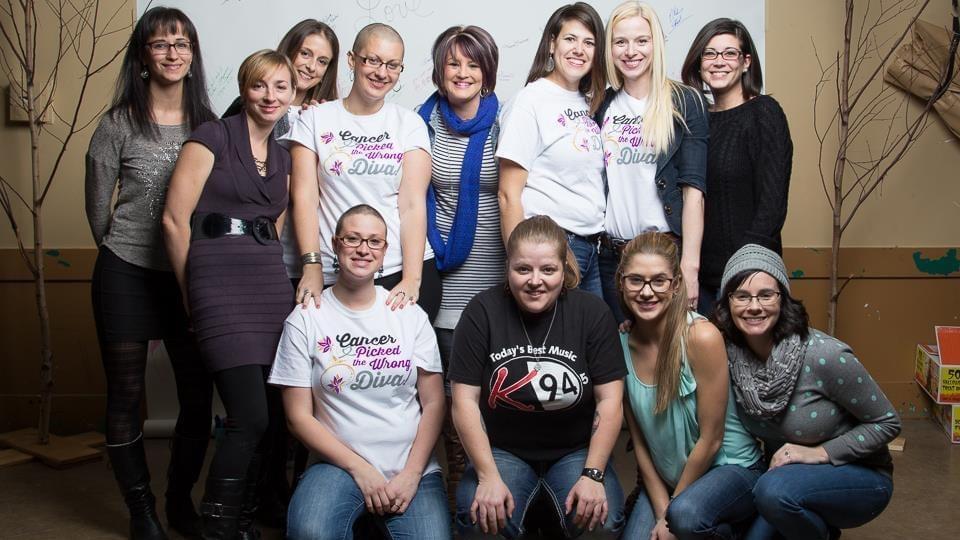 """Rachelle Leger et ses amies avec un chandail portant l'inscription """"le cancer a choisi la mauvaise diva"""", en anglais."""
