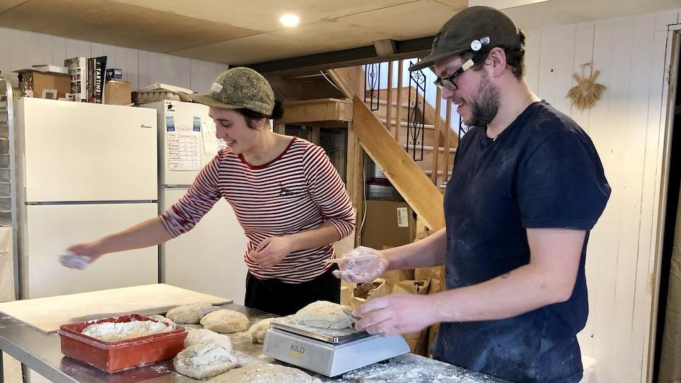 Le couple prépare la pâte des futurs pains à enfourner.