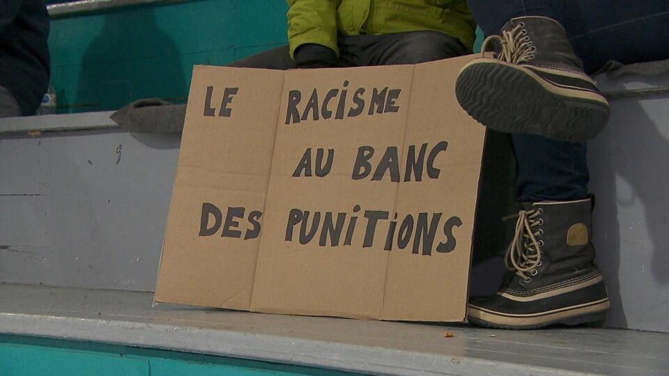 Une pancarte qui dénonce le racisme dans les arénas, au match antiracisme de Gesgapegiag.