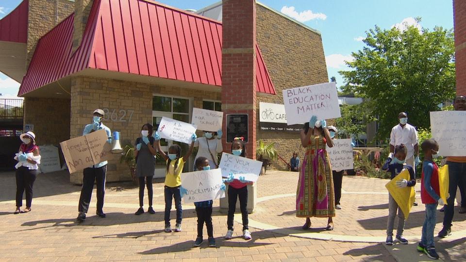 Un groupe de personnes Noires tiennent des pancartes devant un édifice.