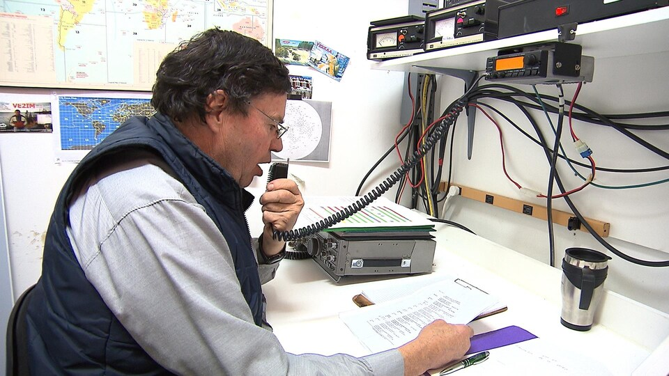 Un homme parle dans un micro de radio amateur.