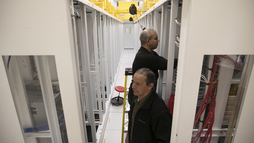 Des techniciens dans une pièce remplie d'équipement technologique.