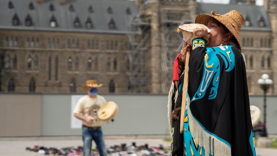 Une femme autochtone en habit traditionnel devant le Parlement à Ottawa.