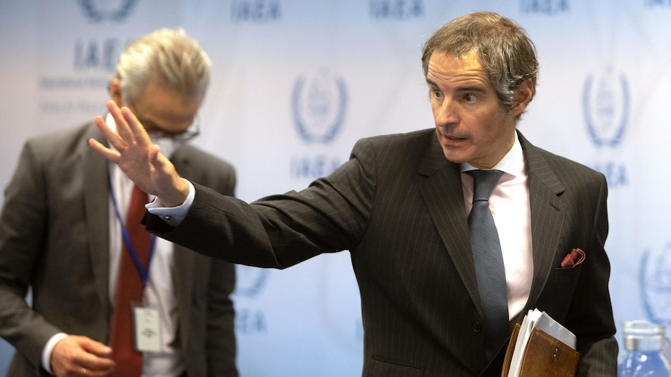 Rafael Grossi, tenant un dossier dans sa main gauche, fait un geste de la main droite.