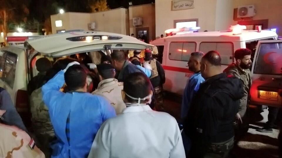 Des médecins et des soldats s'affairent à l'arrière d'une ambulance.