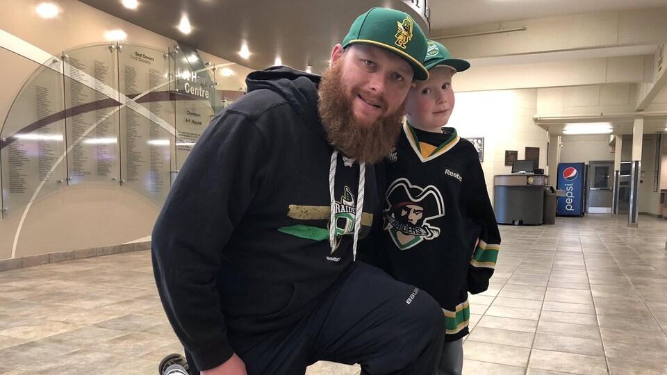 Un père et son fils avec un chandail des Raiders.