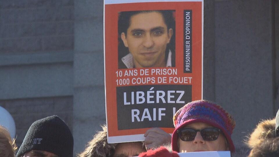 Une personne tient une pancarte de Raif Badawi dans ses mains.