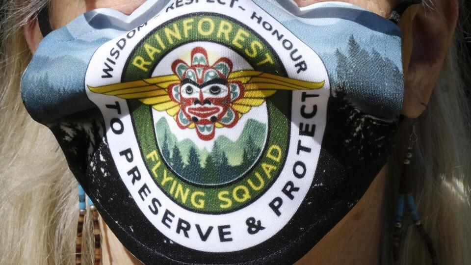 Une manifestante porte un masque aux couleurs du groupe Rainforest Flying Squad.