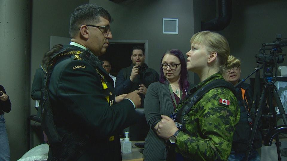 Rakesh Jetly parle à la capitaine, une jeune femme blonde, qui porte un uniforme militaire et un harnais.