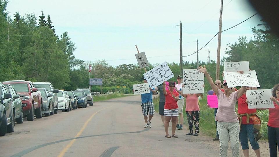 Personnes agitant des affiches en bordure de la route menant au camping.