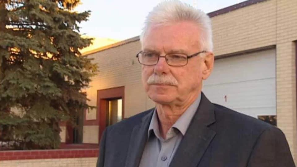 Un homme aux cheveux blancs et à la moustache blanche pose devant une bâtisse aux briques jaunes.