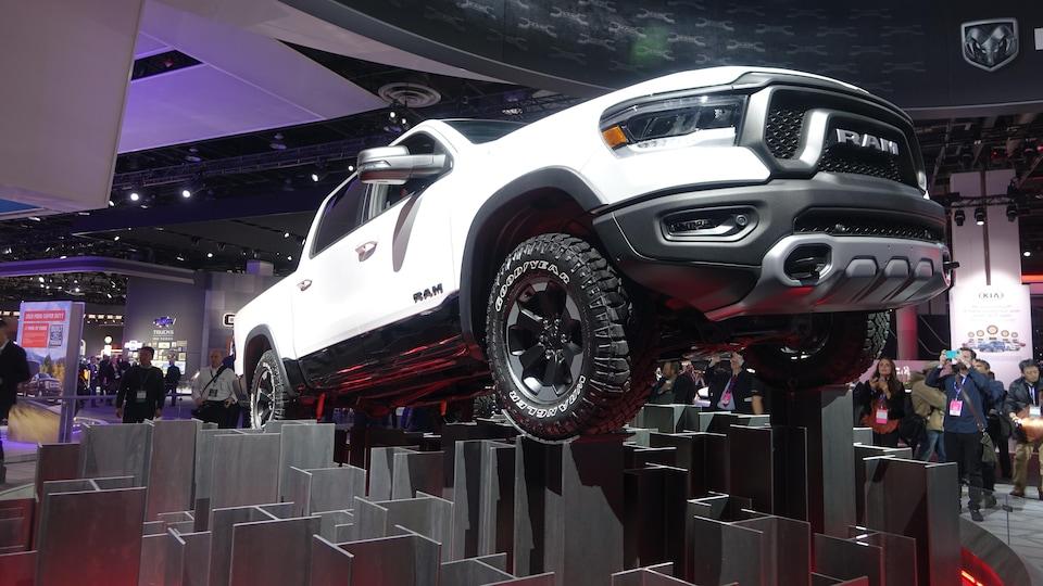 Un camion est installé sur des piliers en métal dans une salle d'exposition