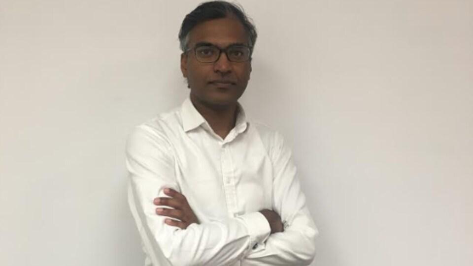 Ram Rammaya pose pour la photo, il a les bras croisés, il porte une chemise blanche et un pantalon noir avec une ceinture noire. Il a la peau foncée, il porte des lunettes, il a les cheveux noirs avec un peu de blanc sur les bords.