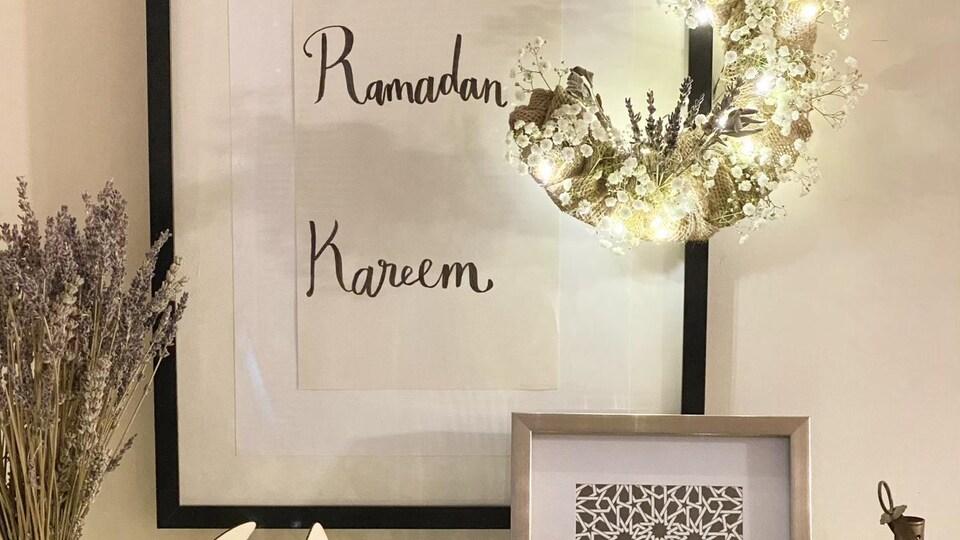 Il est écrit Ramadan Kareem dans un cadre blanc et ivoir accroché au mur. Des fleurs séchées, une lanterne, un petit cadre et une pièce d'art en forme de lune et d'étoiles sont diposés sur un meuble.