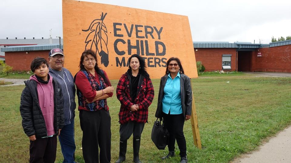 Un groupe devant une pancarte: chaque enfant compte.