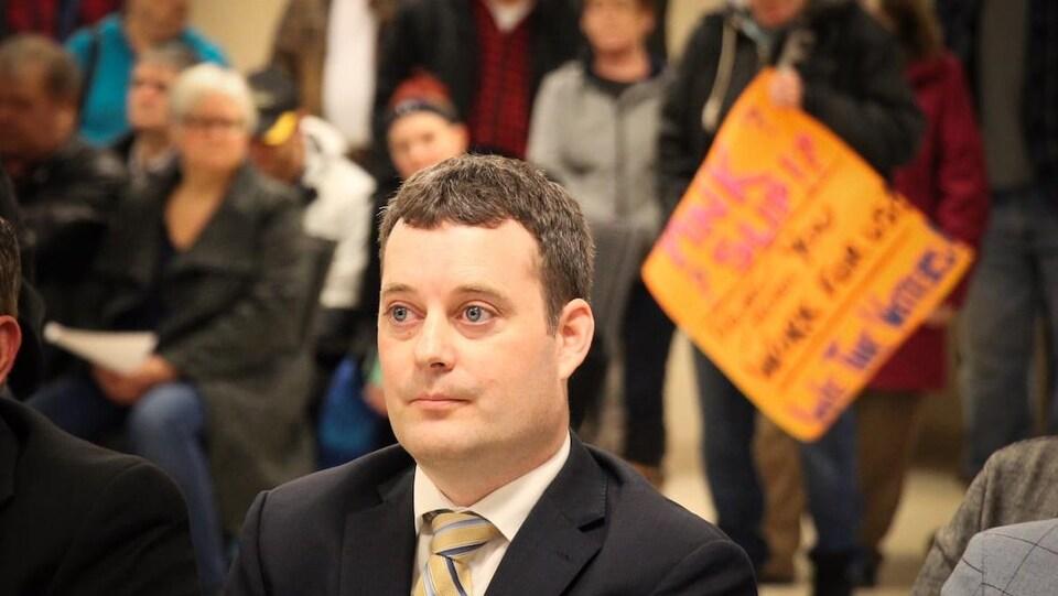 Le ministre Delorey entouré de manifestants.