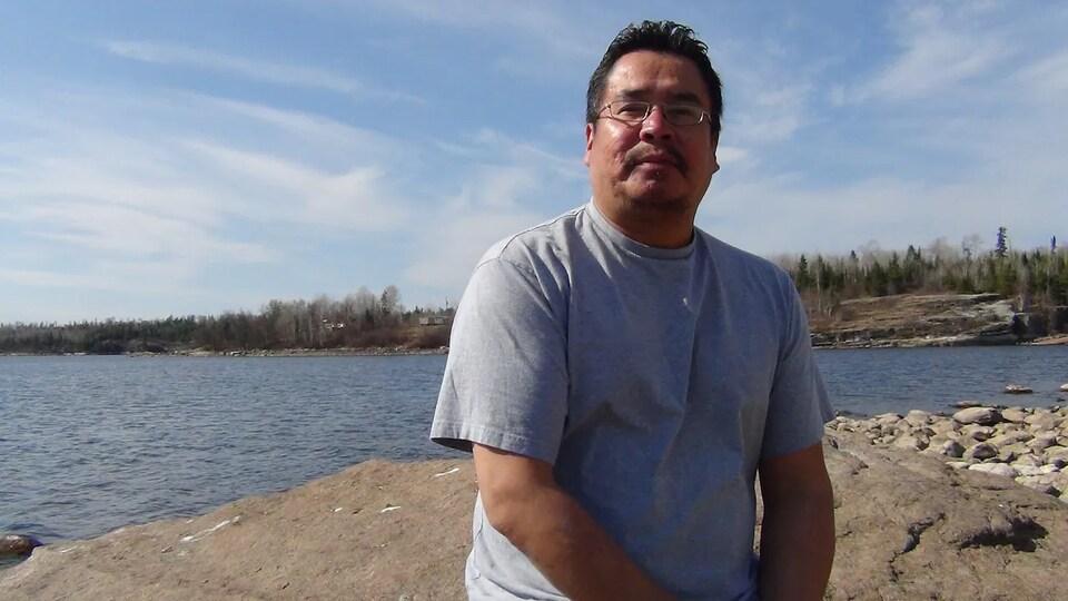 Randy Fobister est devant un lac.